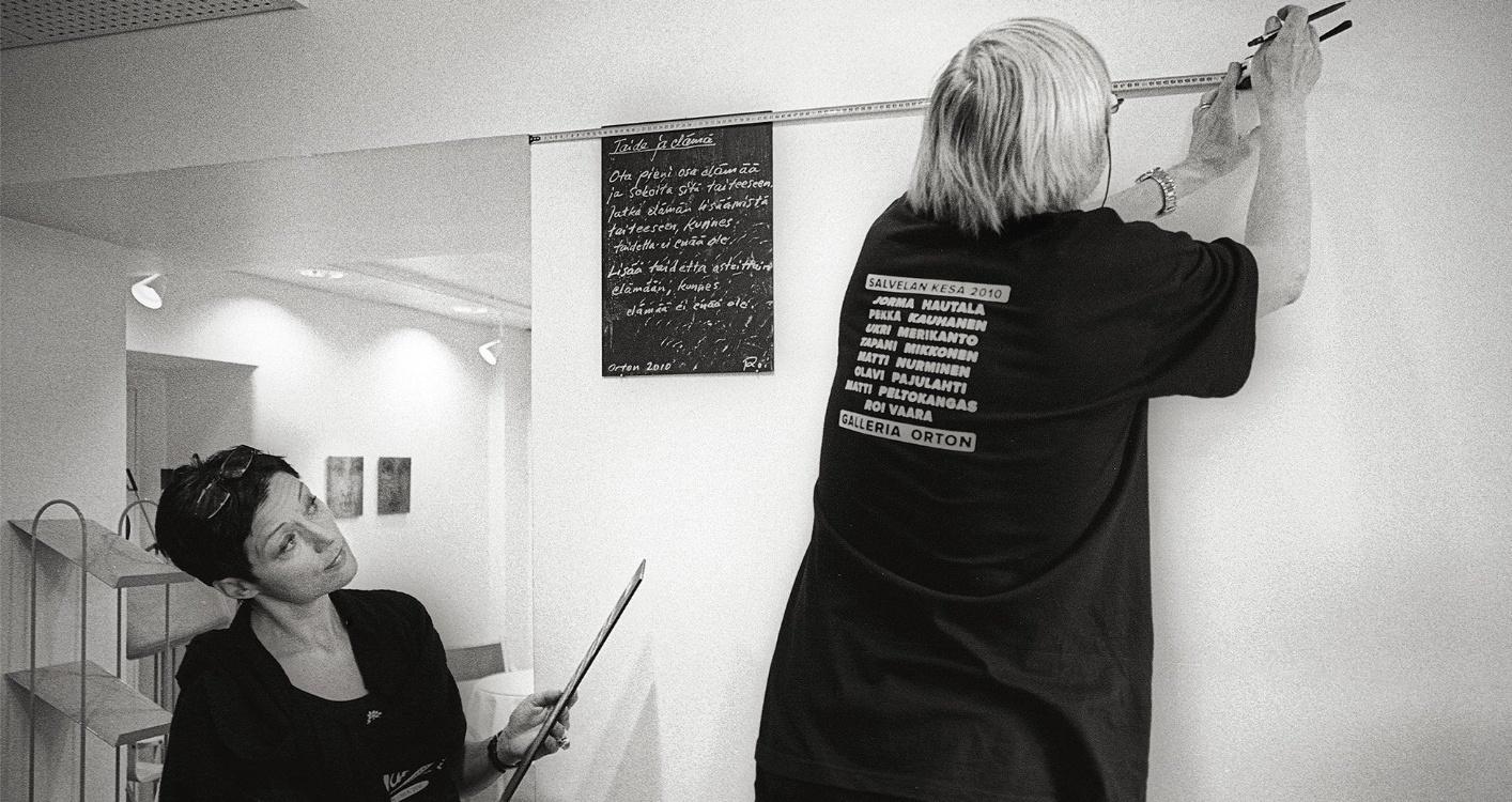 Kuva Galleria Liven kesänäyttelyn ripustuksesta. Kuvassa galleristi Sirpa Viljanen ja taidemaalari Olavi Pajulahti.