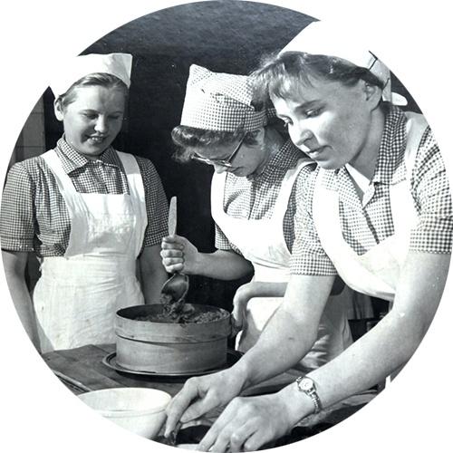 Kolme naista valmistelee ruokaa koulukeittiössä.