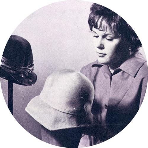 Työklinikalla nainen huovuttaa hattuja.