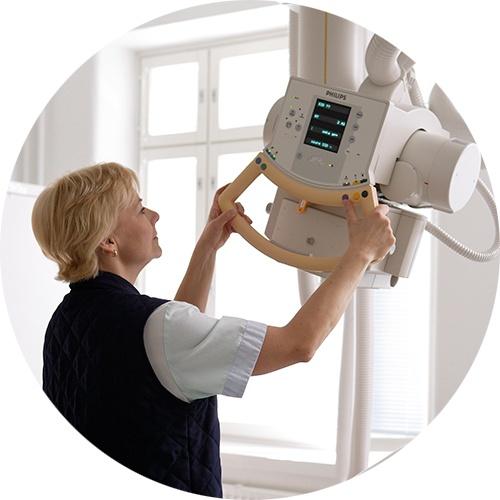 Sairaala Ortonin röntgenhoitaja säätää laitteita.